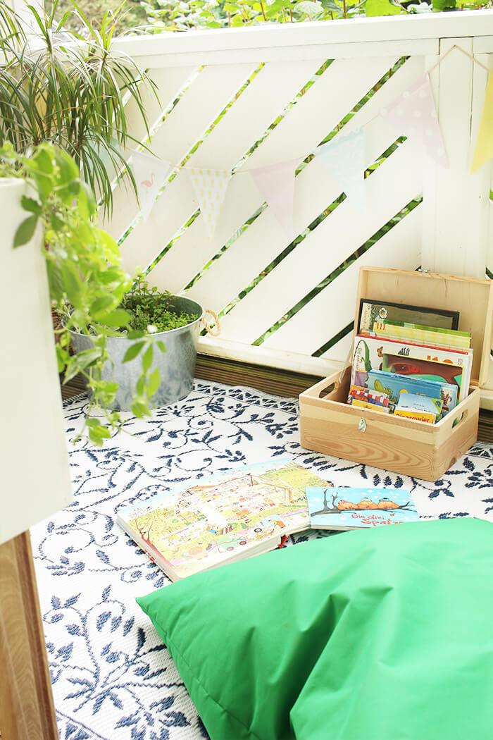 Gemütlicher Balkon für Kinder, mit Outdoorteppich und Sitzkissen.