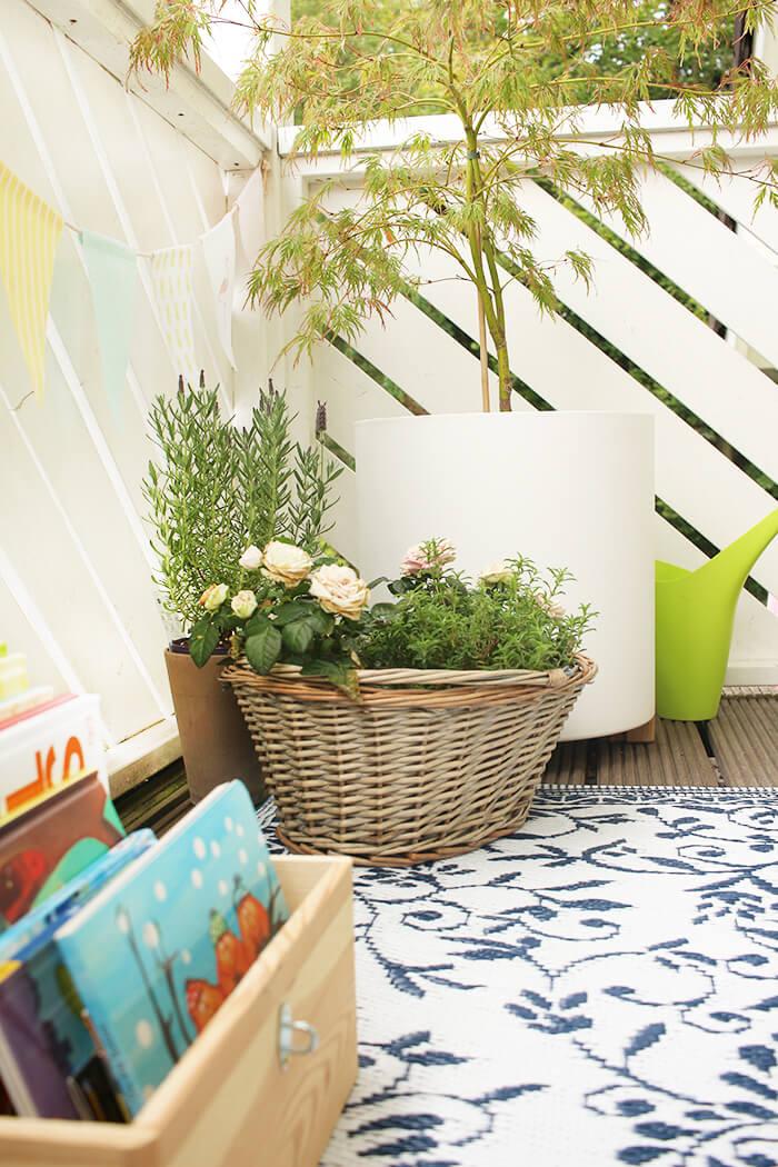 Gemütlicher Balkon mit Outdoorteppich und vielen Pflanzen.