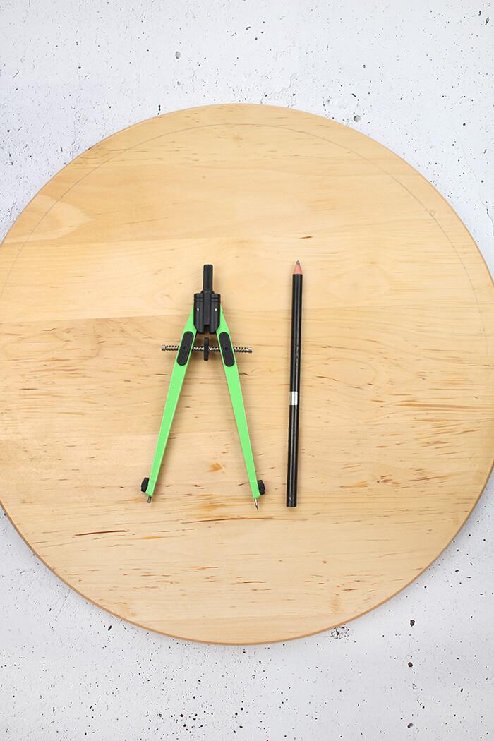 Mit dem Zirkel wird ein Kreis auf das Holz gezeichnet