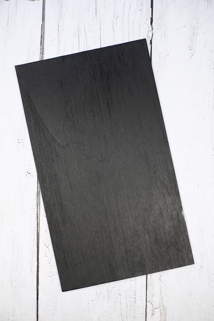 Eine Holzplatte wird schwarz angemalt