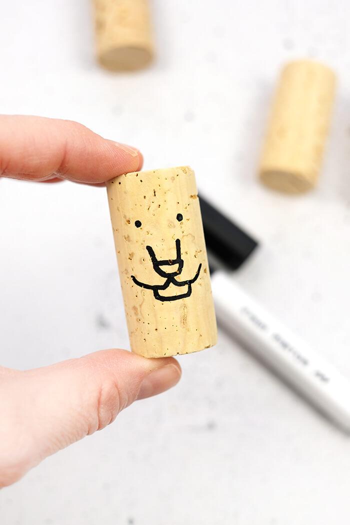 Gesichter mit Marker auf Korken zeichnen